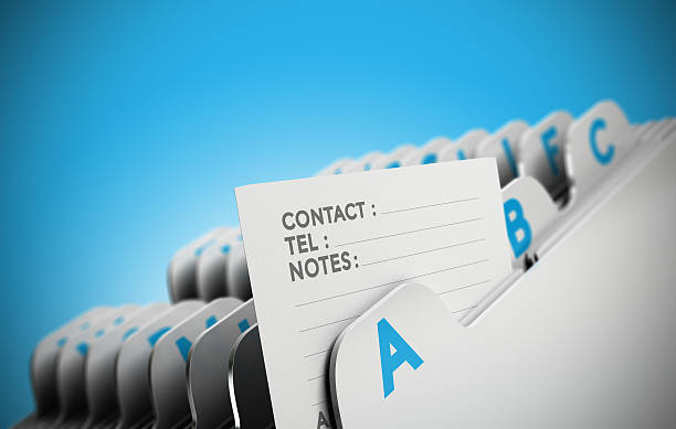 Customer File Concept Folder tab organized alphabetically with focus on a contact note, blue background. Conceptual business image for illustration of customer file, client data management or address list. telephone directory stock pictures, royalty-free photos & images