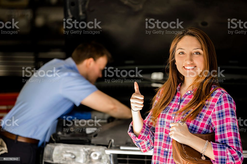 Customer gives auto mechanic a happy thumbs-up for great service. stock photo
