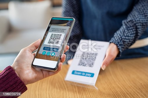 Close up of young woman hand holding smartphone and scanning qr code for digital payment. Customer paying money online using mobile phone after shopping. Girl using cellphone scanner to scan qr code in a coffee shop.