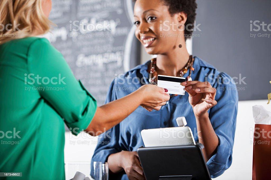 Customer handing cashier a payment card stock photo