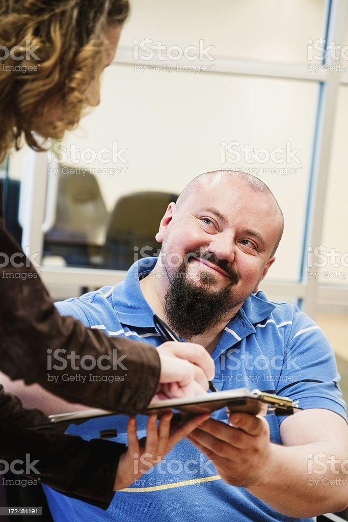 Customer happily signs registration in office lobby royalty-free stock photo
