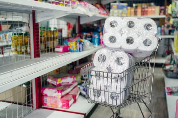 Customer hoarding tissue, toilet paper on shopping cart in retailer stock photo