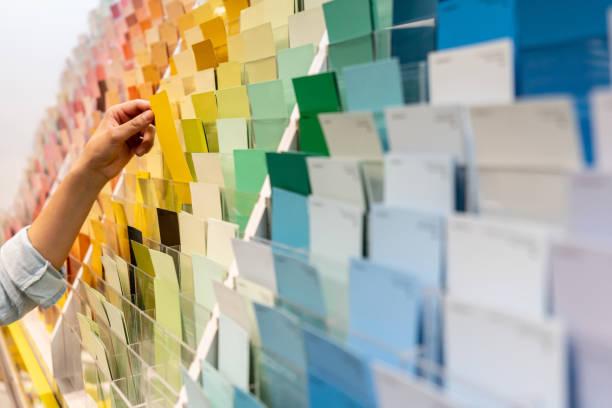 klant die een kleurensteekproef bij een huis verbetering opslag houdt - kleurenwaaier stockfoto's en -beelden
