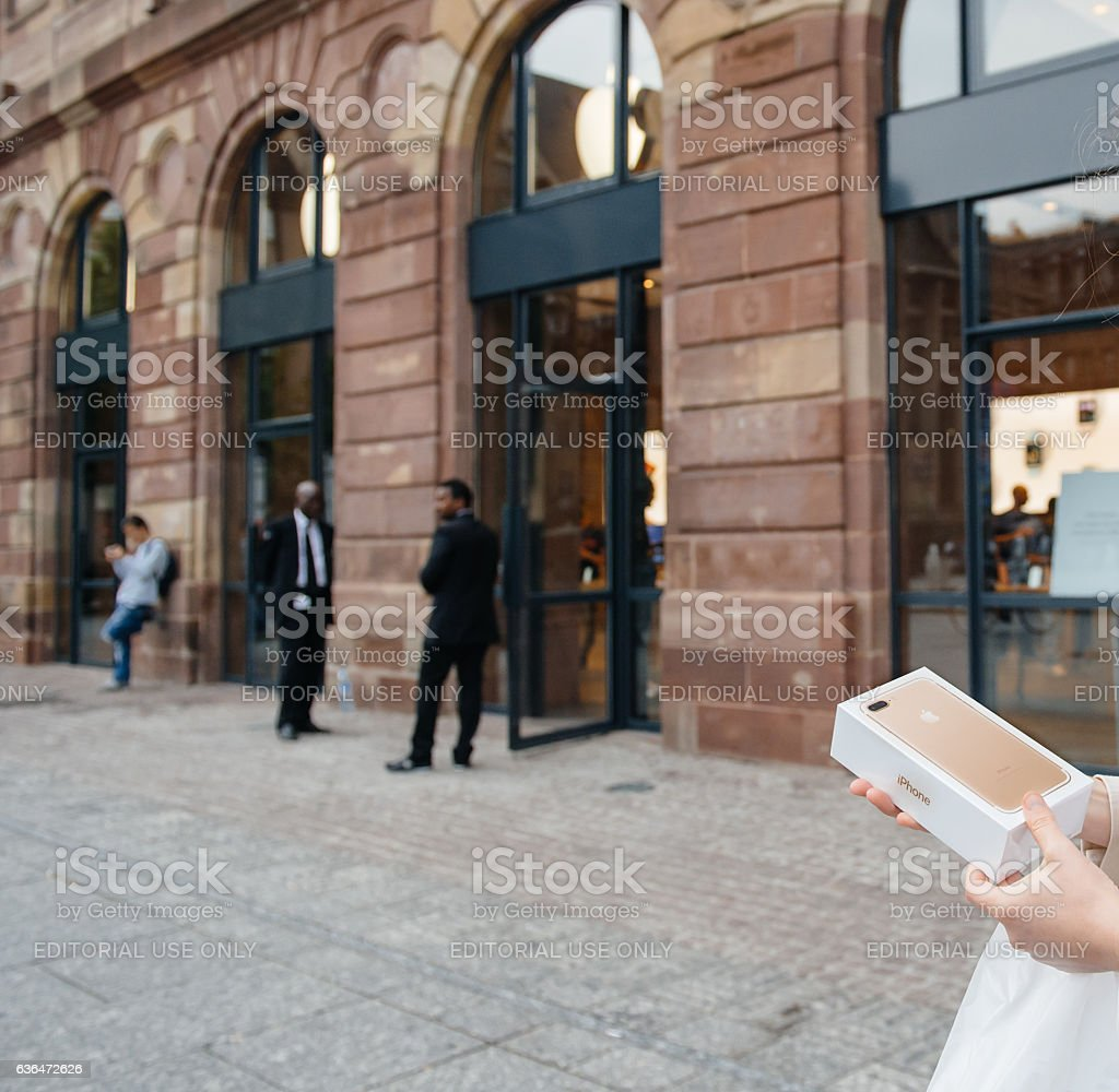 Customer holding box of new iPhone front of Apple Store stock photo