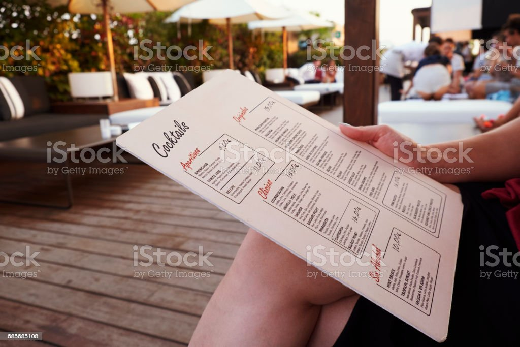BARCELONA - JULY 29, 2016: Customer holds La Isabela Hotel'u2019s rooftop bar menu, mid section Lizenzfreies stock-foto
