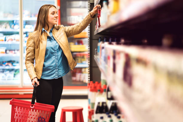 customer in alcohol or drinks section in supermarket or liquor store holding a bottle from the shelf. happy lady with shopping basket choosing alcoholic beverages. - prateleira compras imagens e fotografias de stock