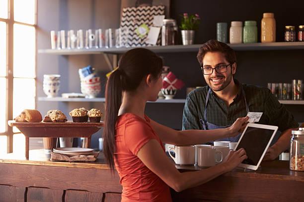 お支払いのお客様には、コーヒーショップを使用して、デジタルタブレットを持っているリーダ - 小売販売員 ストックフォトと画像