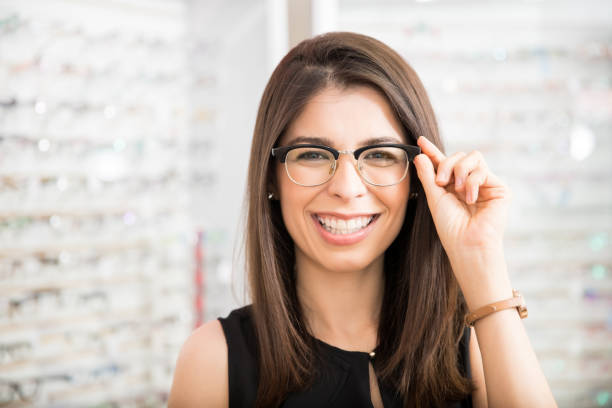 Customer in optician's shop choosing the right frame for eyeglasses Portrait of beautiful young woman trying new glasses in optician store optical instrument stock pictures, royalty-free photos & images