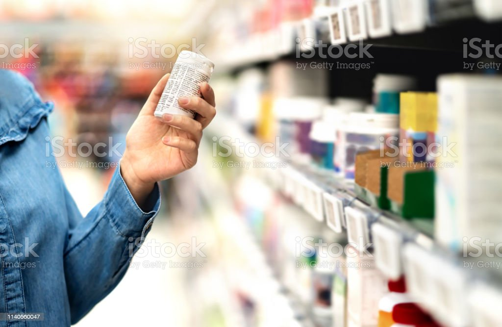 Customer in pharmacy holding medicine bottle. Woman reading the label text about medical information or side effects in drug store. Patient shopping pills for migraine or flu. - Royalty-free Adulto Foto de stock
