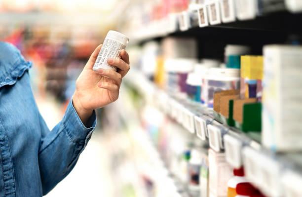 kunde in der apotheke mit arzneimittelflasche. frau, die den etikettentext über medizinische informationen oder nebenwirkungen im drogeriemarkt liest. patienten einschoppen pillen für migräne oder grippe. - nahrungsergänzungsmittel stock-fotos und bilder