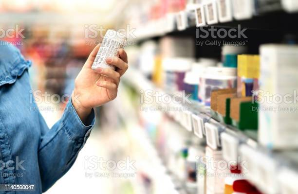 Customer In Pharmacy Holding Medicine Bottle Woman Reading The Label Text About Medical Information Or Side Effects In Drug Store Patient Shopping Pills For Migraine Or Flu - Fotografias de stock e mais imagens de Adulto
