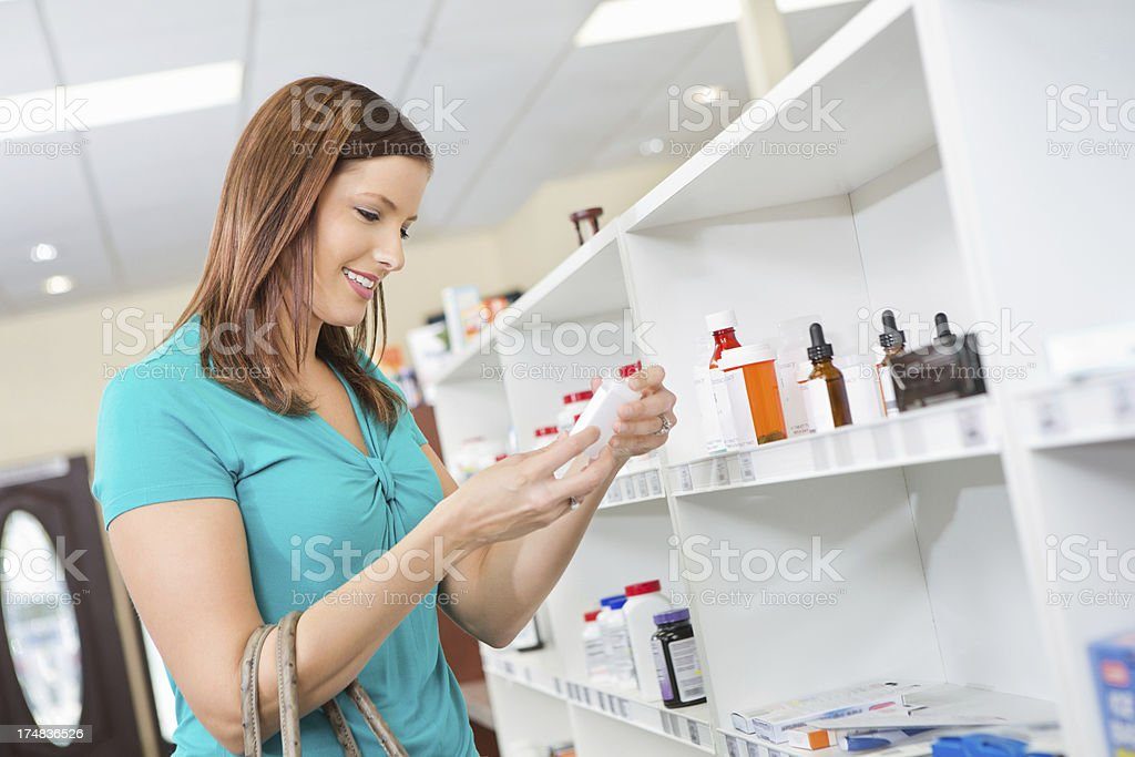 Customer in pharmacy reading medication labels side effects royalty-free stock photo