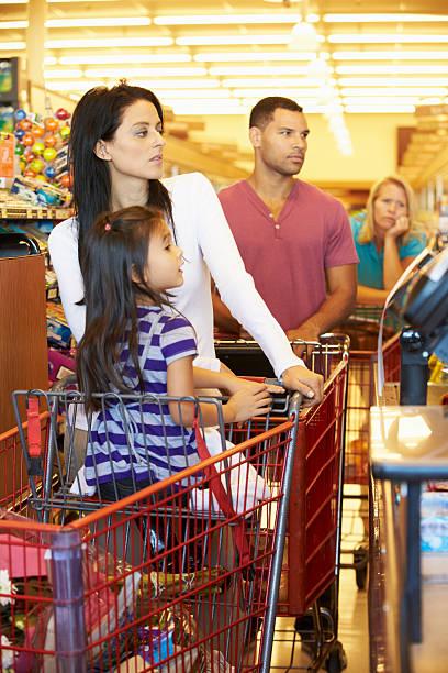client à payer à la file d'attente pour le shopping au supermarché de départ - queue photos et images de collection