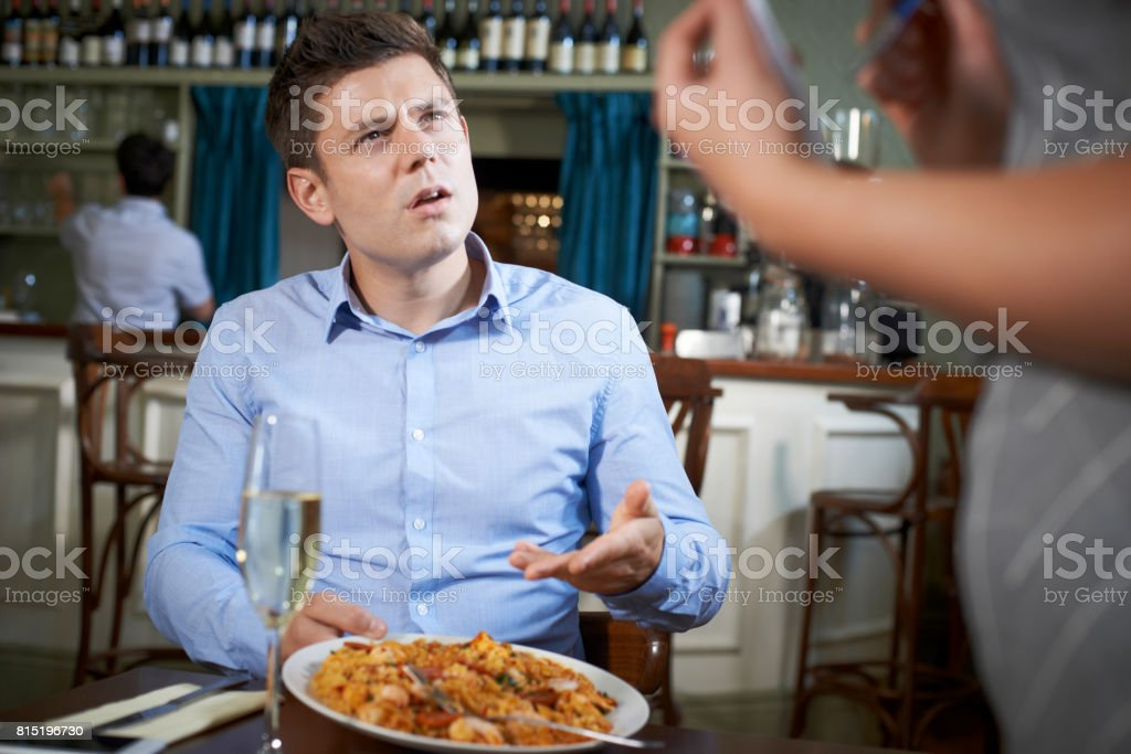 Customer In Restaurant Complaining To Waitress About Food stock photo