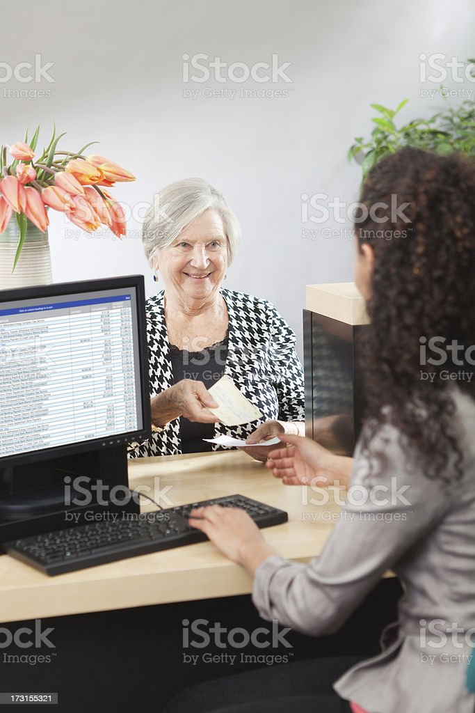 A bank customer making a transaction with a bank teller in a retail...