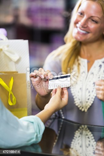 536272741istockphoto Customer in retail store paying cashier with gift card 470168414