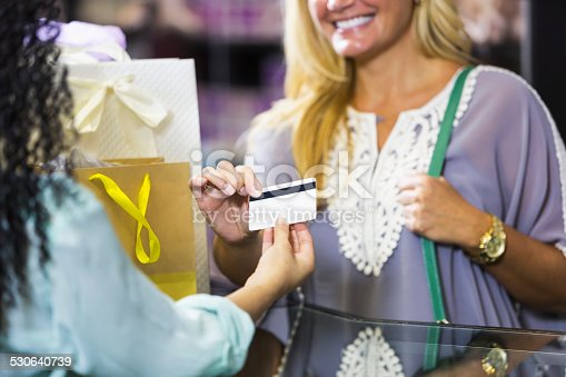 istock Customer in retail store paying cashier with gift card 530640739
