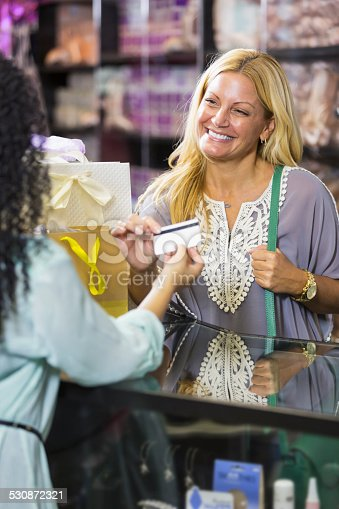 536272741istockphoto Customer in retail store paying cashier with gift card 530872321