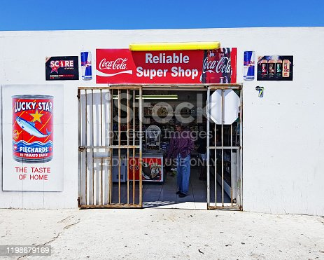 Cape Town, South Africa - December 16, 2019: A shopper leaves a small convenience store in the lower-middle-class suburb of Grassy Park. Such shops, typically operated by recent immigrants from the Indian subcontinent or countries further north in Africa, have mushroomed across South Africa in recent decades.