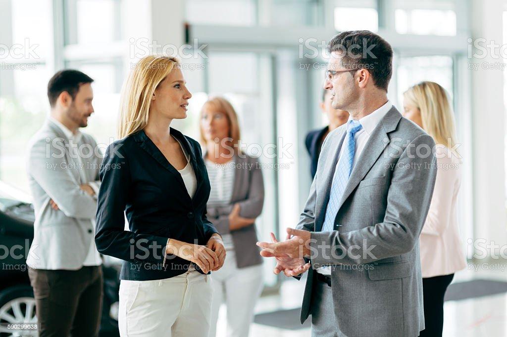 Customer looking at cars at dealership royaltyfri bildbanksbilder