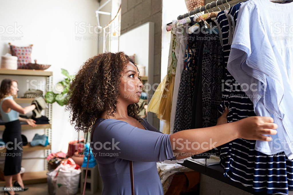 Customer looking at clothes on a hanging rail in a boutique stock photo