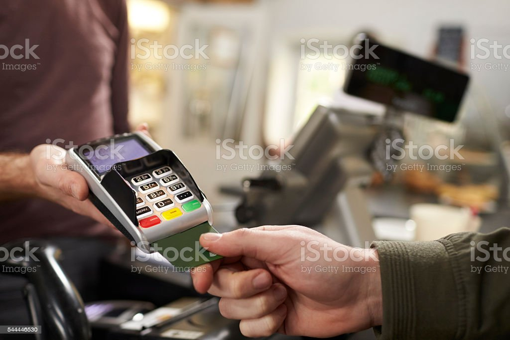 Customer makes credit card payment over counter at a cafe stock photo