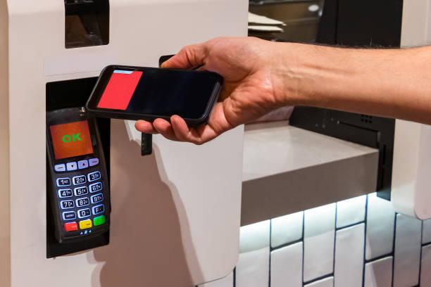 Customer making a NFC contact less payment with his mobile at a fast food restaurant stock photo