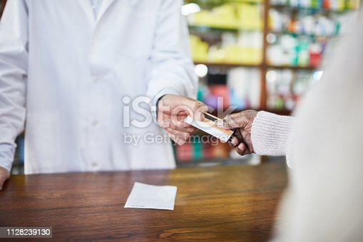 Close up of chemist taking the credit card from customer at checkout counter. Customer making cashless payment at pharmacy.