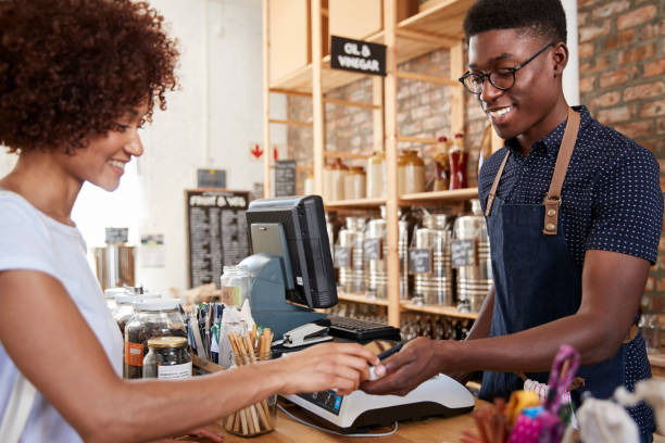 Customer Making Contactless Payment For Shopping At Checkout Of Grocery Store Using Mobile Phone Customer Making Contactless Payment For Shopping At Checkout Of Grocery Store Using Mobile Phone sales clerk stock pictures, royalty-free photos & images