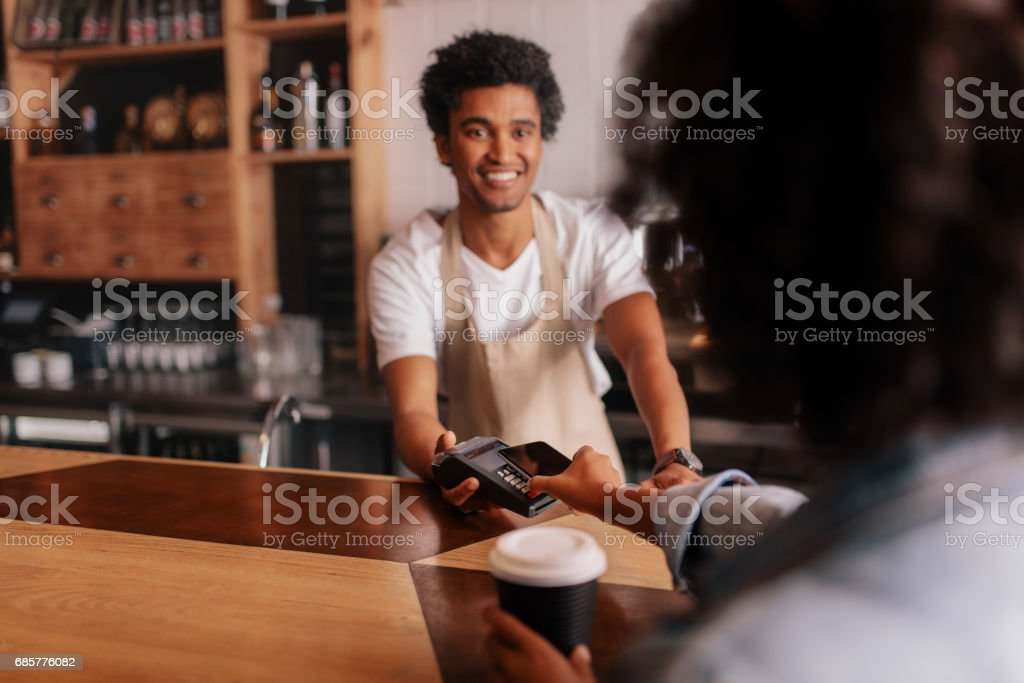 Customer making payment through mobile phone at counter in cafe stock photo