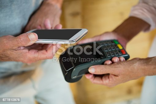 istock Customer making payment through NFC technology on mobile phone 677810976
