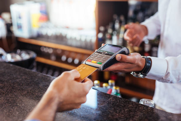 Customer making payment using credit card at bar Customer making payment using credit card. Close up of card payment being made between customer and bartender in cafe. credit card purchase stock pictures, royalty-free photos & images