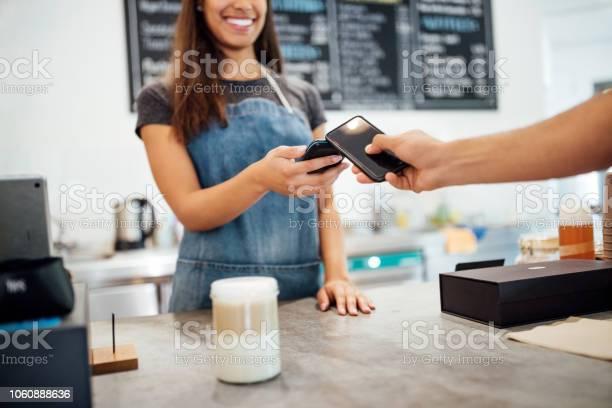 Customer making payment using nfs technology at cafe picture id1060888636?b=1&k=6&m=1060888636&s=612x612&h=kxv3r7289wi3viuovpt54xqiy0fgzwkspuxj3ojjjhm=