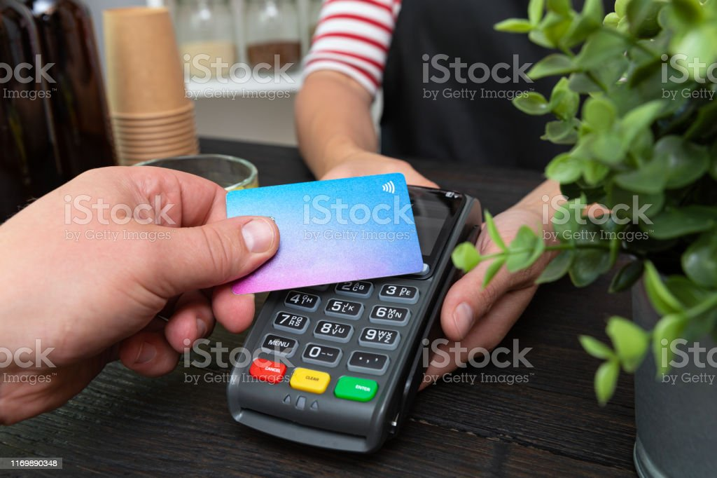 Customer making wireless or contactless payment using credit card Customer making wireless or contactless payment using credit card Apron Stock Photo