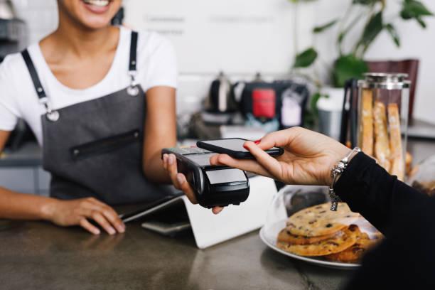客戶使用智慧手機在咖啡館進行無線支付 - 付錢 個照片及圖片檔