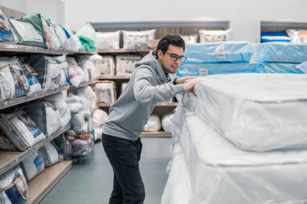 customer man chooses bed linen in the supermarket mall store. - bed furniture stock pictures, royalty-free photos & images