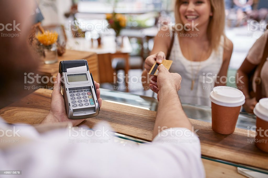 Customer paying at a cafe with credit card bildbanksfoto