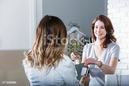 536272741istockphoto Customer paying at checkout counter in store 471345094