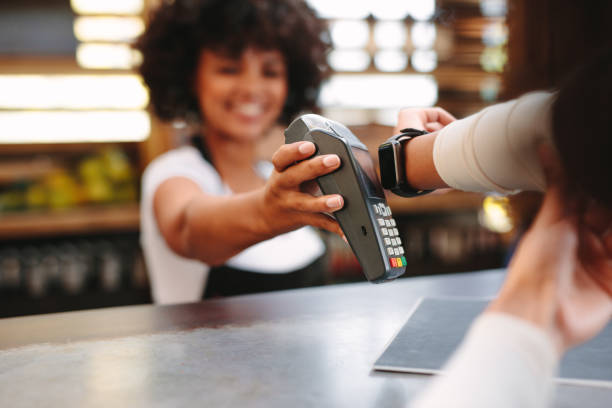 customer paying bill using a smartwatch - contactless payment stock pictures, royalty-free photos & images