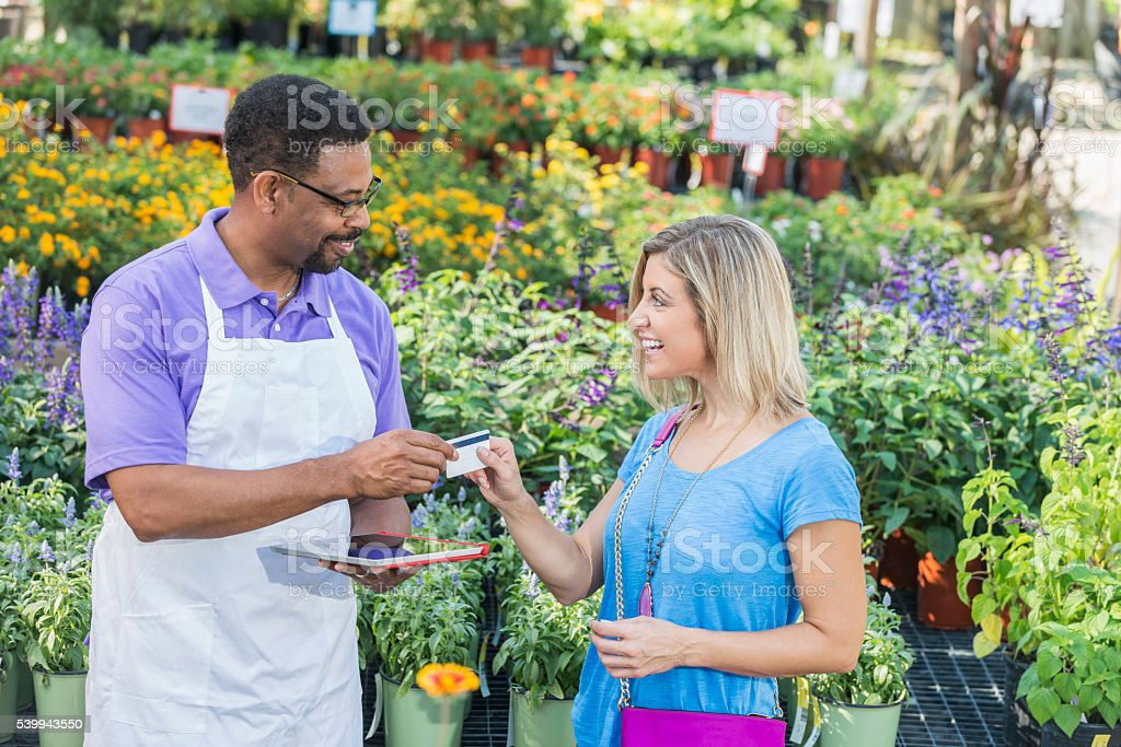 Customer paying by credit card in garden store stock photo