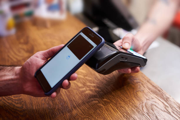 Customer paying by smartphone with NFC technology stock photo
