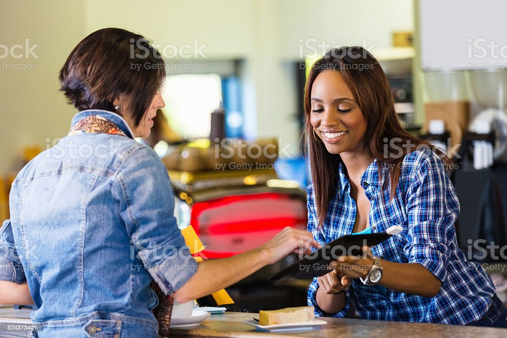 Customer paying for coffee with digital tablet credit card reader stock photo