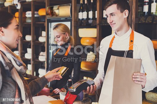 istock Customer paying for order of cheese in grocery shop. 817409164