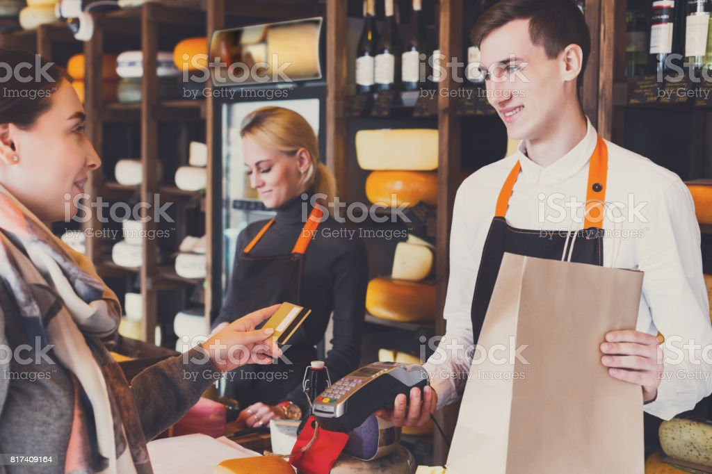 Customer paying for order of cheese in grocery shop. stock photo