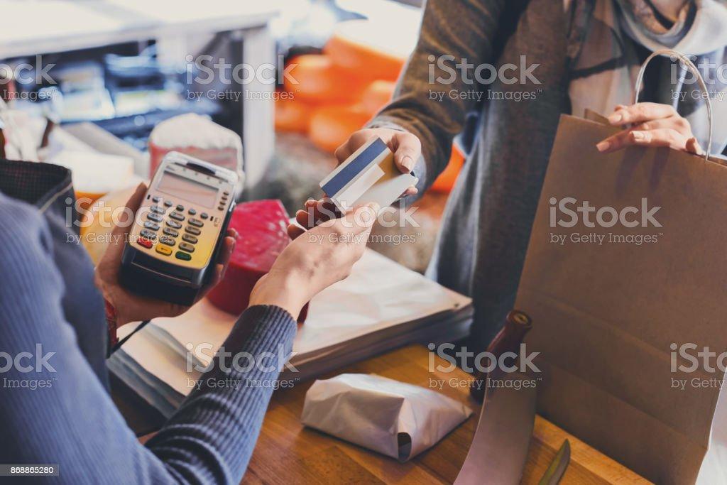 Klant betaalt voor de volgorde van de kaas in kruidenier. - Royalty-free Aankoop met creditcard Stockfoto