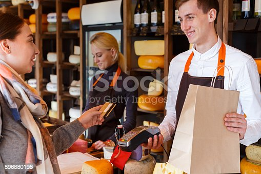 istock Customer paying for order of cheese in grocery shop. 896880198