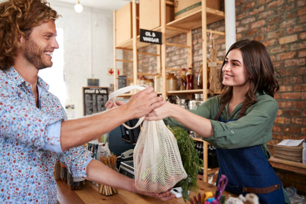 Customer Paying For Shopping At Checkout Of Sustainable Plastic Free Grocery Store Customer Paying For Shopping At Checkout Of Sustainable Plastic Free Grocery Store social responsibility stock pictures, royalty-free photos & images