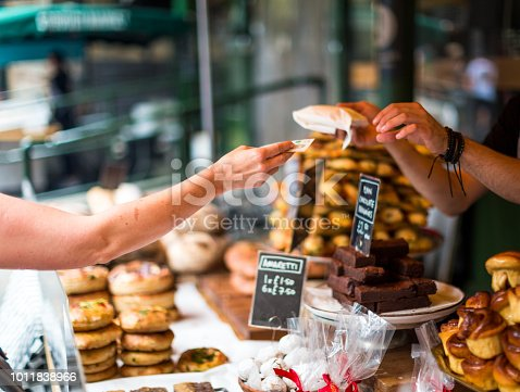 Close up color image depicting a cash transaction between a customer and the owner of a bakery stall at an outdoor food market in London, UK. The customer is paying using a five pound note for what appears to be some kind of cake or pastry. In the background the contents of the market stall - cakes, brownies, sweet pastries - are blurred out of focus. Room for copy space.