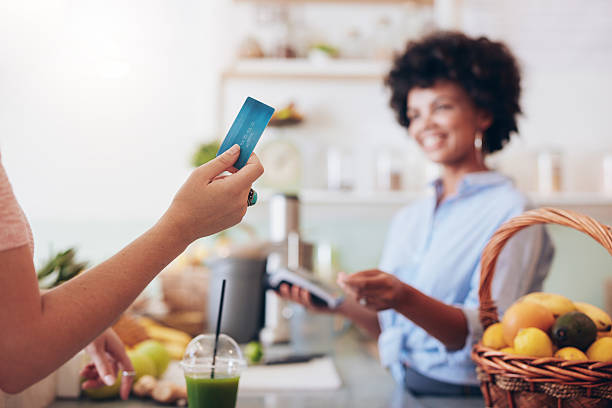customer paying for their order with a credit card - paying with card contactless imagens e fotografias de stock