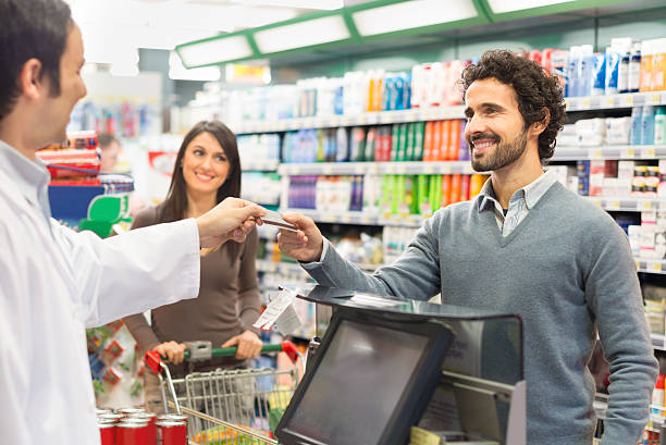 Customer paying the bill in a supermarket Customer using a credit card to pay in a supermarket grocer stock pictures, royalty-free photos & images